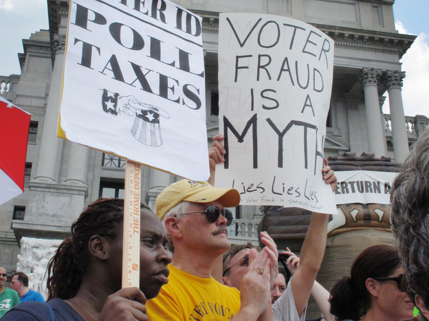 Demonstrators hold signs at an NAACP-organized rally on the steps of the Pennsylvania Capitol to protest the state's new voter identification law on July 24 in Harrisburg, Pa. (AP)