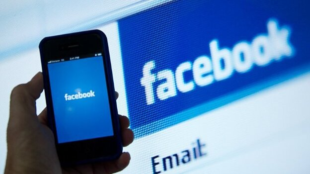 An illustration of an Apple iPhone displaying the Facebook app's splash screen in front of the login page. (AFP/Getty Images)