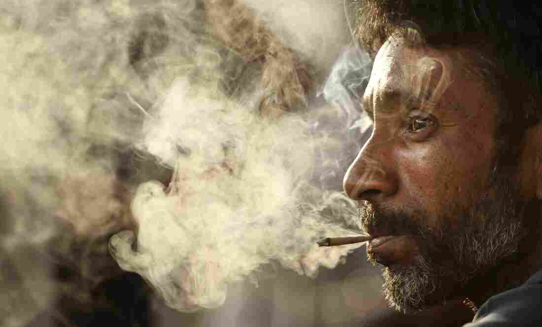 """A man smokes a bidi on """"No Tobacco Day,"""" May 31, in Allahabad, India. These small, hand-rolled cigarettes are popular in India and Bangladesh because they are far cheaper than regular cigarettes."""