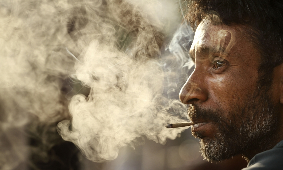 "A man smokes a bidi on ""No Tobacco Day,"" May 31, in Allahabad, India. These small, hand-rolled cigarettes are popular in India and Bangladesh because they are far cheaper than regular cigarettes."