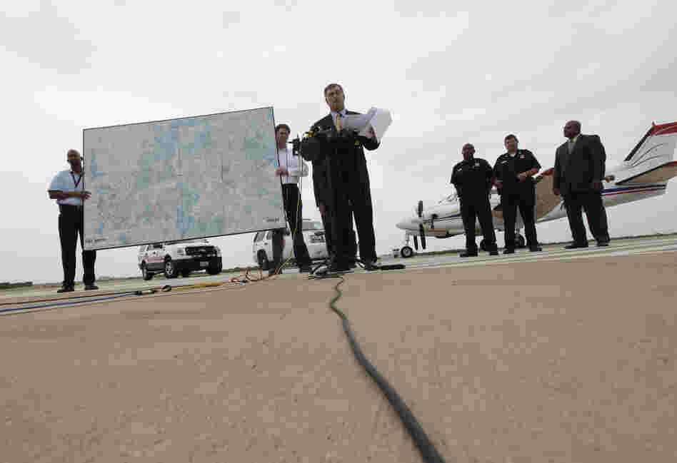 Dallas Mayor Mike Rawlings, center, holds a news conference in front of a plane that will be used for aerial spraying in Dallas.