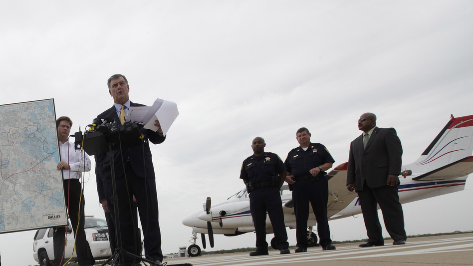 Dallas Mayor Mike Rawlings, center, holds a news conference in front of a plane that will be used for aerial spraying in Dallas. (AP)