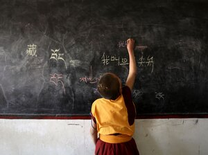 A lama student writes Chinese characters on a blackboard during a class on November 1, 2007 in D