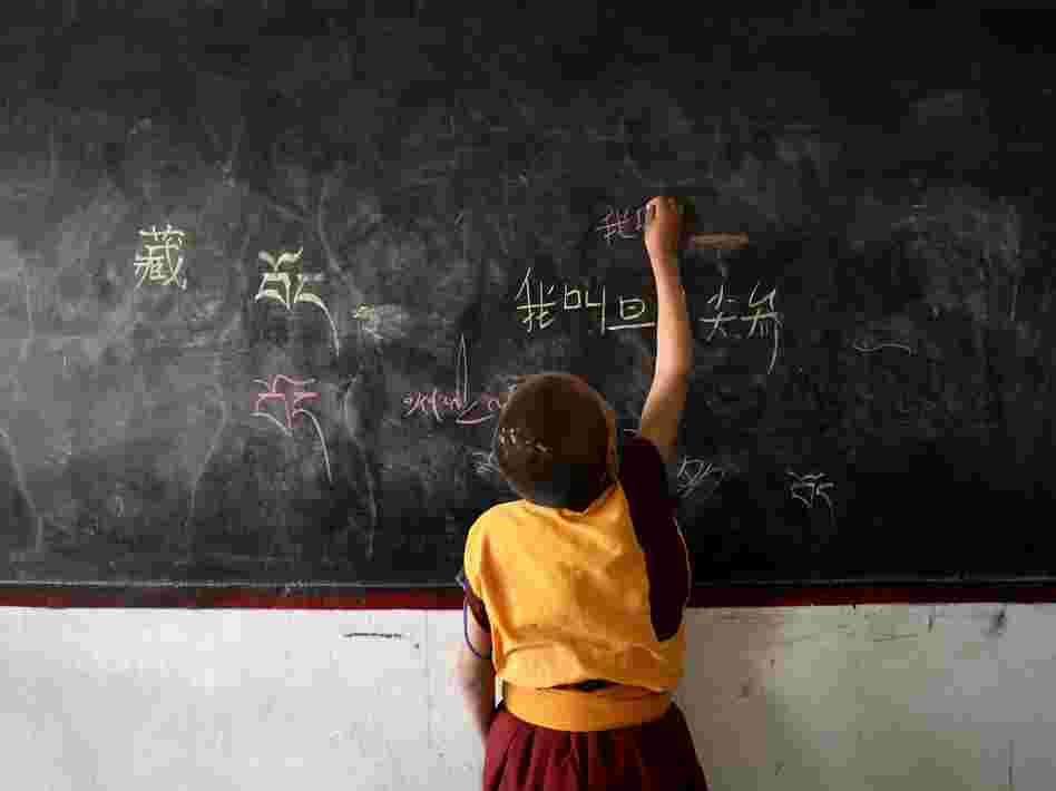 A lama student writes Chinese characters on a blackboard during a class on November 1, 2007 in Dari County of Guoluo Prefecture, Qinghai Province, northwest China.