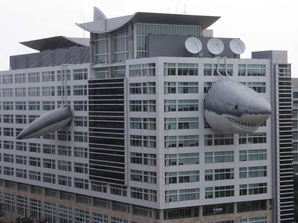 Chompie, a giant inflatable shark that measures 446 feet long, peeks out of the global headquarters building of Discovery Communications. (PR Newswire)
