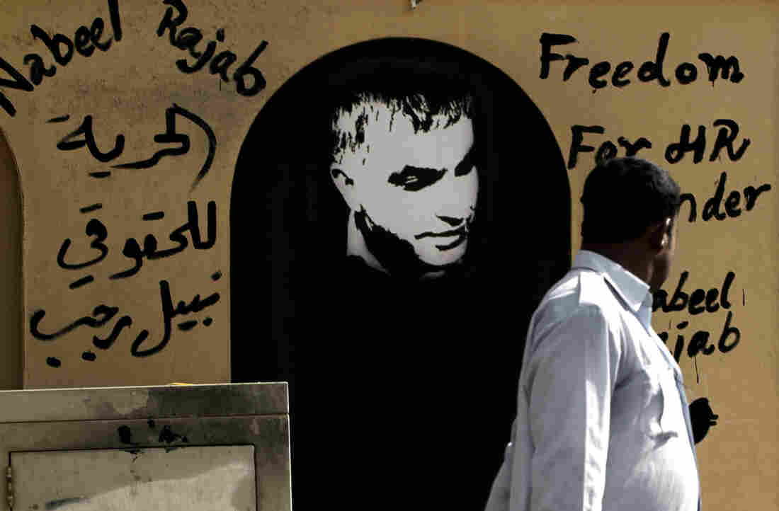 """A man walks past a picture of human rights defender Nabeel Rajab and Arabic that reads, """"freedom to human rights defender Nabeel Rajab."""""""