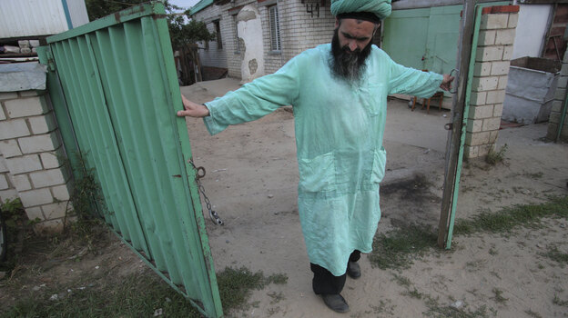 Gumar Ganiyev opens the gates of the compound where members of the Islamic sect he belongs to have lived in seclusion since the early 2000s outside Kazan, capital of the Russian province of Tatarstan, earlier this month. (AP)