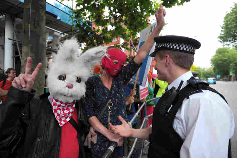 A police officer talks with London protesters.
