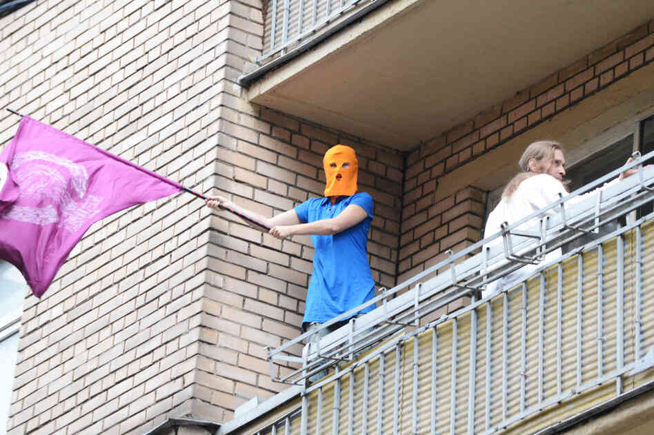 A supporter of feminist punk band Pussy Riot, wearing the group's trademark colored balaclava, waves a flag on a balcony in Moscow on Friday.