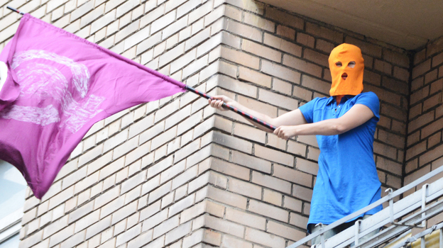 A supporter of feminist punk band Pussy Riot wearing the group's trademark colored balaclava waves a flag on a balcony in Moscow on Friday. (AFP/Getty Images)