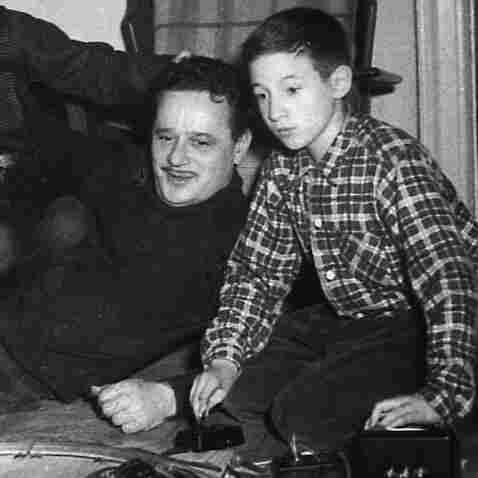 Abel Meeropol watches as his sons, Robert and Michael, play with a train set.