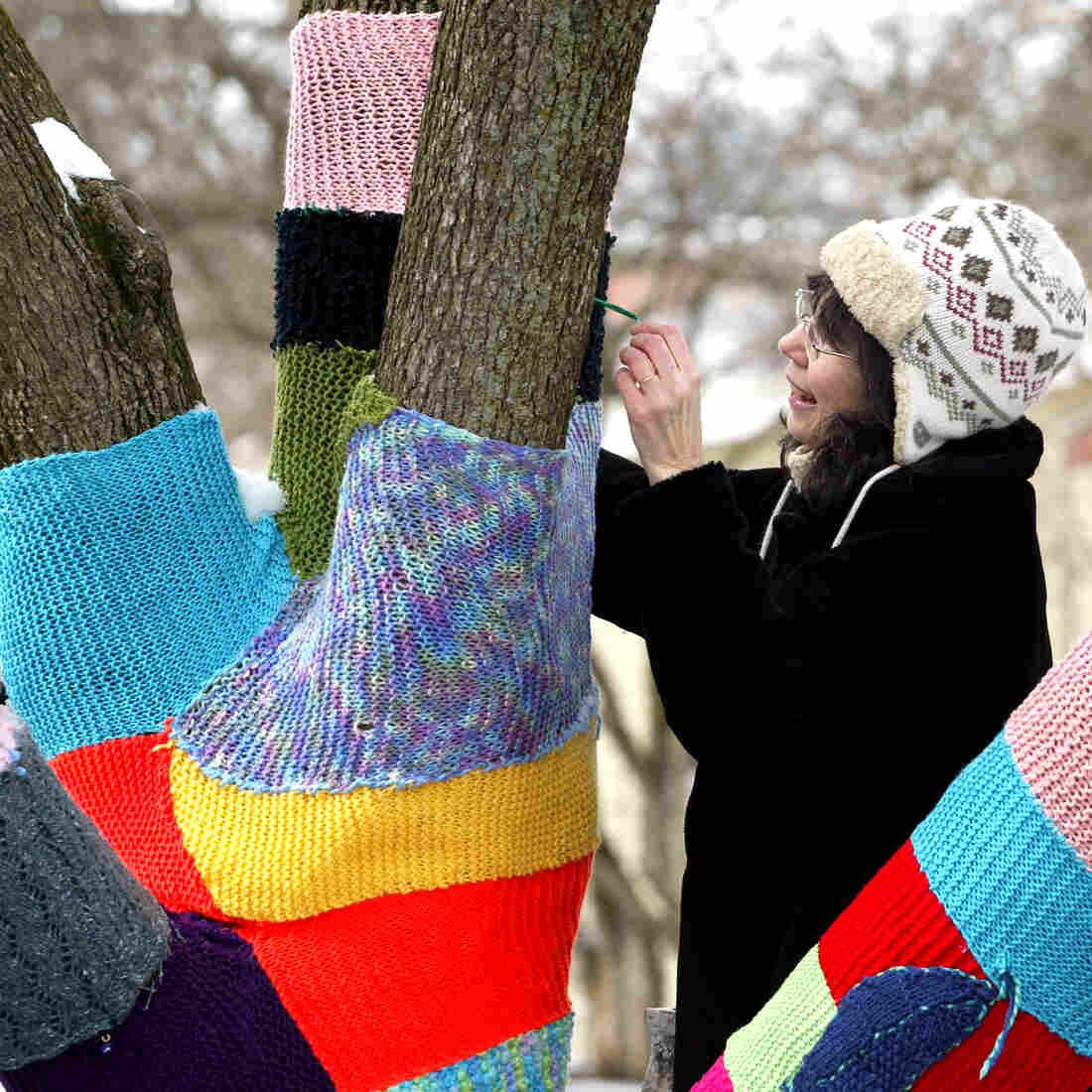 """Nancy Mellon sews another knitted section to the """"Knit Knot Tree"""" on Xenia Avenue in Yellow Springs, Ohio, in February 2008."""