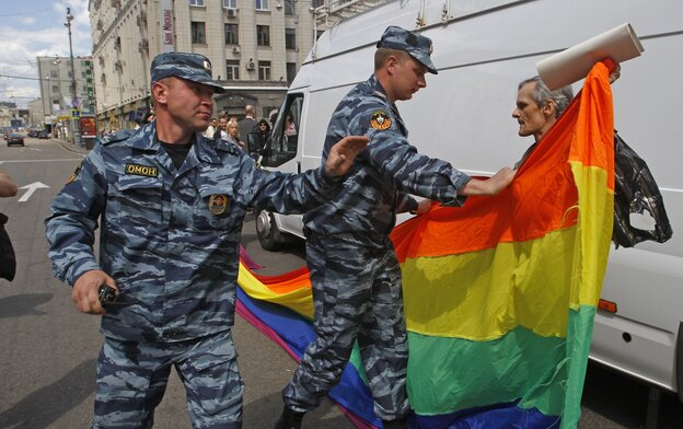 Russian police officers detain a gay rights activist with his flag during an attempt to