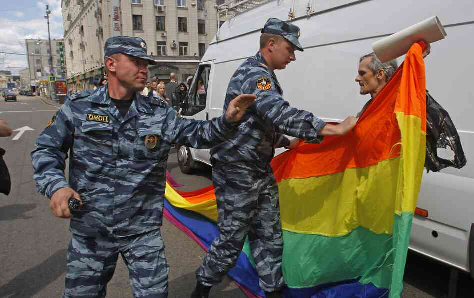 Russian police officers detain a gay rights activist with his flag during an attempt to hold a gay pride