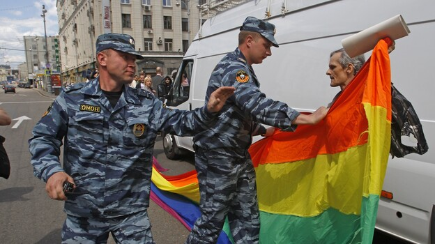 Russian police officers detain a gay rights activist with his flag during an attempt to hold a gay pride parade in Moscow in May. (AP)