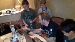 DefCon Kids camp co-founder Chris Hoff, with Conner Gilliam (from left), Conner Fine and Ethan Lai, work on a machine that draws designs on ping-pong balls. The camp is held in Las Vegas.