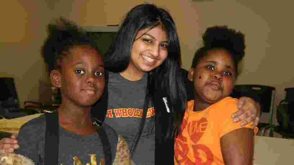Austin College student Naureen Dharani, center, with new friends at an afterschool program.