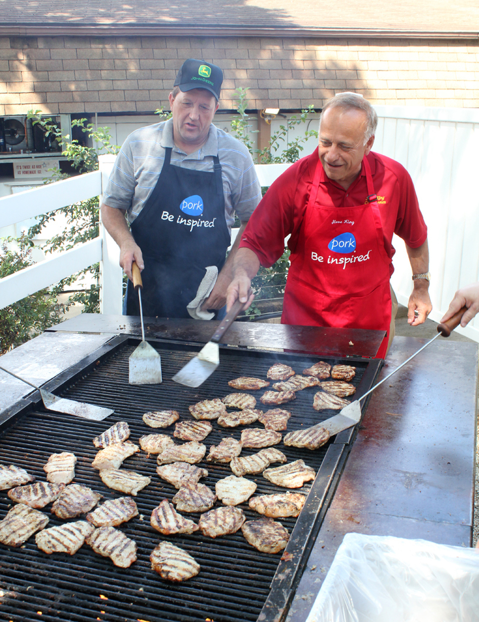 Republican Rep. Steve King of Iowa (right) flips pork chops at the Iowa State Fair in Des Moines while Terry Aupperle of Wiota watches. Aupperle lives in Cass County. He can't vote for King anymore because of redistricting.