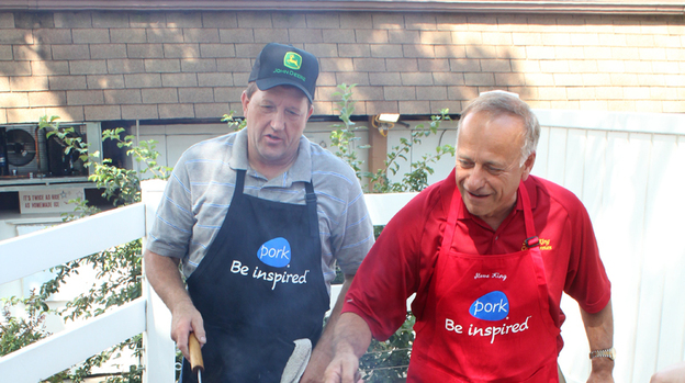Republican Rep. Steve King of Iowa (right) flips pork chops at the Iowa State Fair in Des Moines while Terry Aupperle of Wiota watches. Aupperle lives in Cass County. He can't vote for King anymore because of redistricting. (Iowa Public Radio)