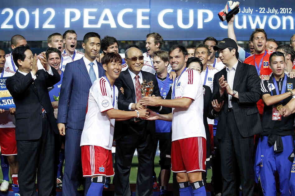 Captain Heiko Westermann (third right) and Son Heung-Min (third left) of Hamburger hold the trophy with Moon, as they celebrate after winning the Peace Cup final match.