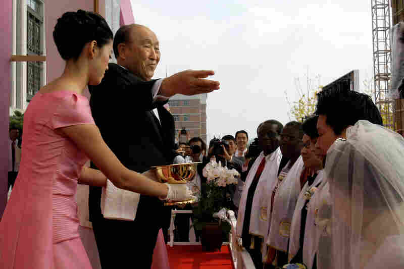 Moon spreads holy waters during a mass wedding ceremony arranged by his Unification Church at Sun Moon University in Asan, south of Seoul, South Korea, in October 2009.