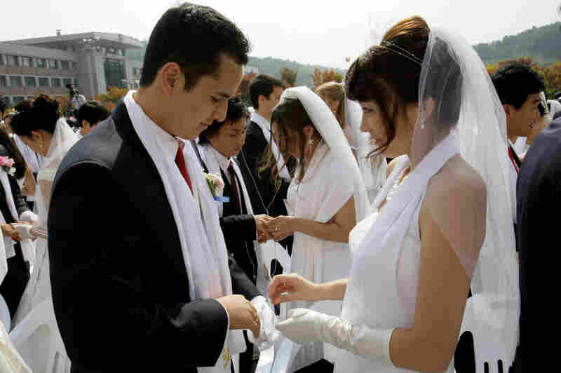 Bridegroom Uriah Buscovich from California and his bride, Moona Field from Argentina, exchange their wedding rings during the mass wedding ceremony.
