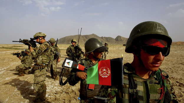 Afghan soldiers (right) patrol with U.S. troops in the Panjwai district of southern Afghanistan in May. The two armies have been working together for years, but Afghan attacks against U.S. and NATO forces have been rising recently. (NPR)