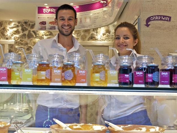 Dimitris Plassas and Georgia Ladopoulou work the yogurt bar at Fresko, which specializes in several varieties of Greek-style yogurt. (NPR)
