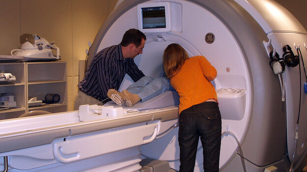 Dr. Amit Etkin and a research assistant help a participant into the bore of the MRI. (Courtesy of the Etkin Lab at Stanford University)