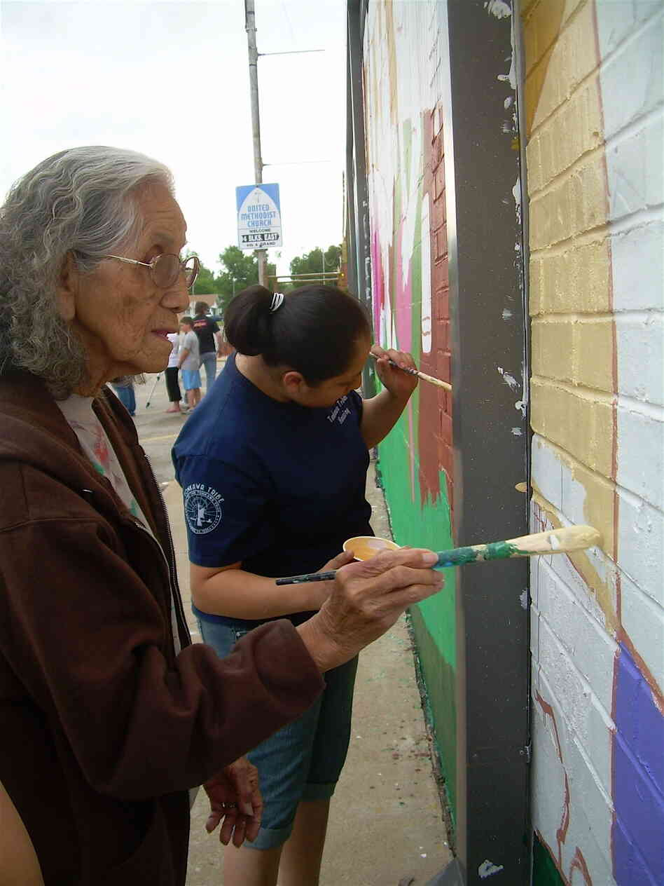 Tonkawa Tribal members add paint to the mural in Oklahoma.