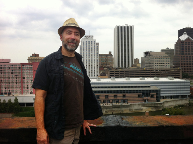 Adam Frank stands atop of the Wilder Building in Rochester, N.Y.