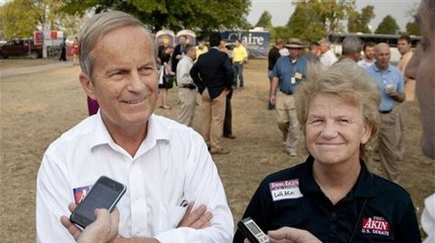 Rep. Todd Akin, R-Mo., and his wife Lulli, talk with reporters last Thursday at the Missouri State Fair in Sedalia, Mo. On Monday, Akin was resisting GOP calls to resign from his Senate race.
