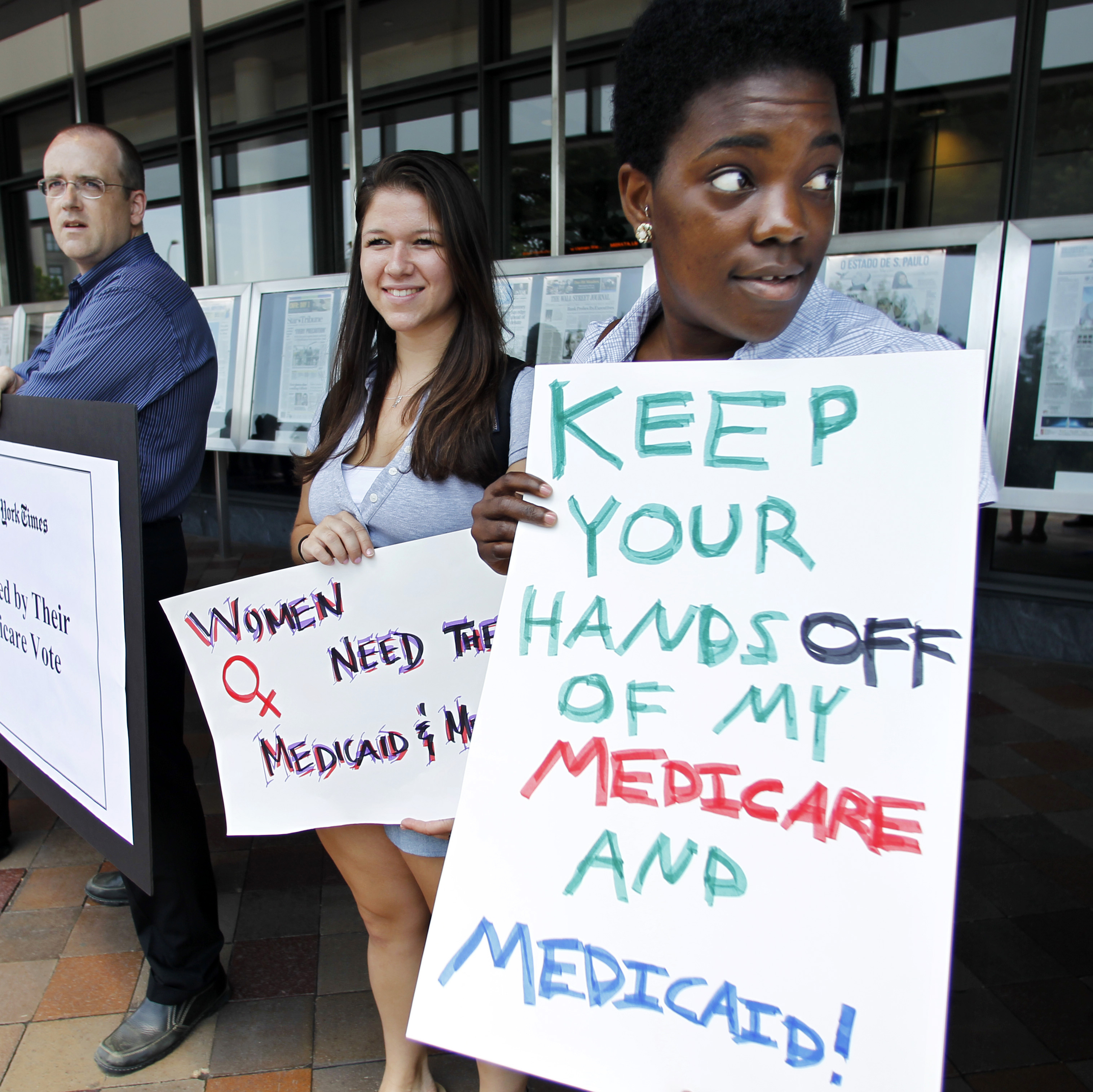 Dena Robinson, from right, and Hannah Hoffman, join dozens of Medicare advocates gathered outside the Newseum in Washington, D.C., during a demonstration on June 13, 2011.