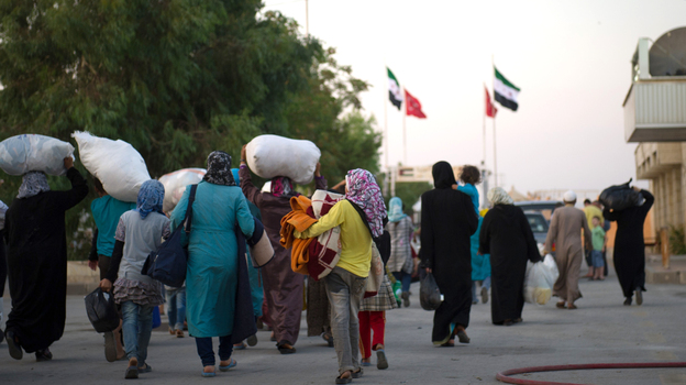 Syrians fleeing increased violence arriving last week at the border between the Syrian town of Azaz and the neighboring Turkish town of Kilis. (AFP/Getty Images)