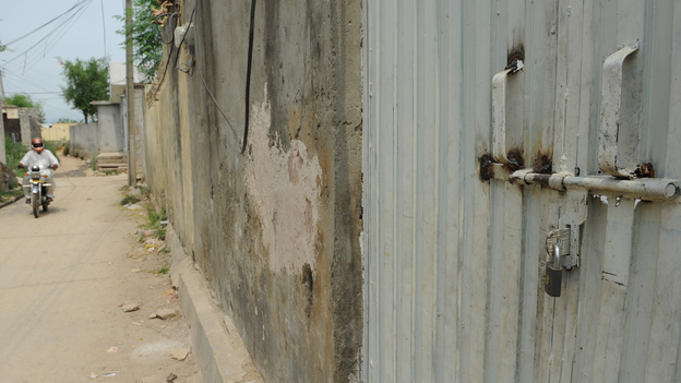 In the Islamabad slum where a Christian girl is accused of burning some Muslim verses, the gate to her family's home is locked and the people who live there have fled. (AFP/Getty Images)