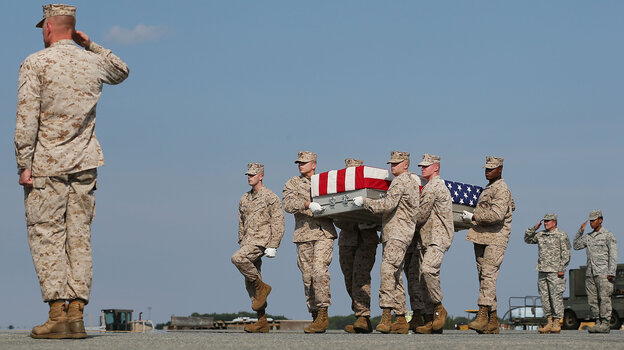 "Aug. 13: At Dover Air Force Base in Delaware, the remains of Marine Lance Cpl. Gregory T. Buckley are carried during a dignified transfer. He was killed in a ""green on blue"" attack."
