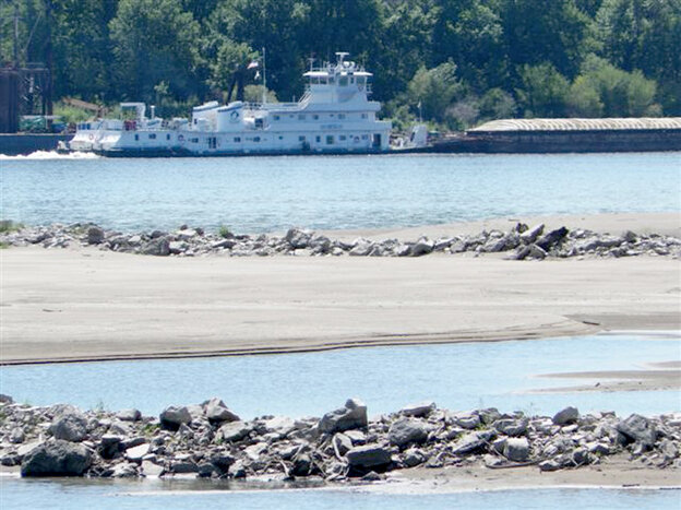 A tow pushes a barge past a sandbar on the Mississi