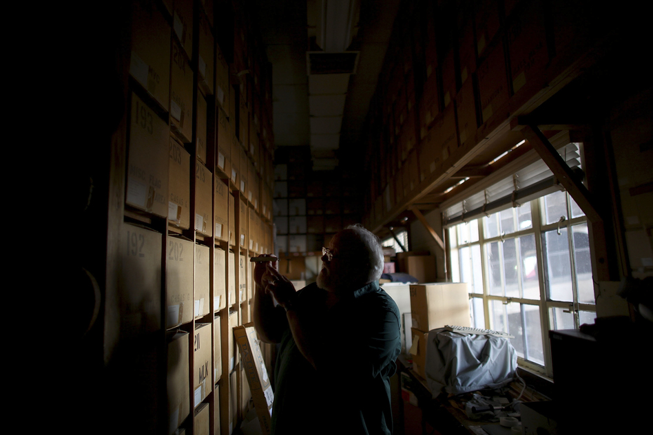 Swetnam stands in the catacombs of storage boxes that house thousands of tree-ring samples. His laboratory is buried under the bleachers of the University of Arizona football stadium. (NPR)