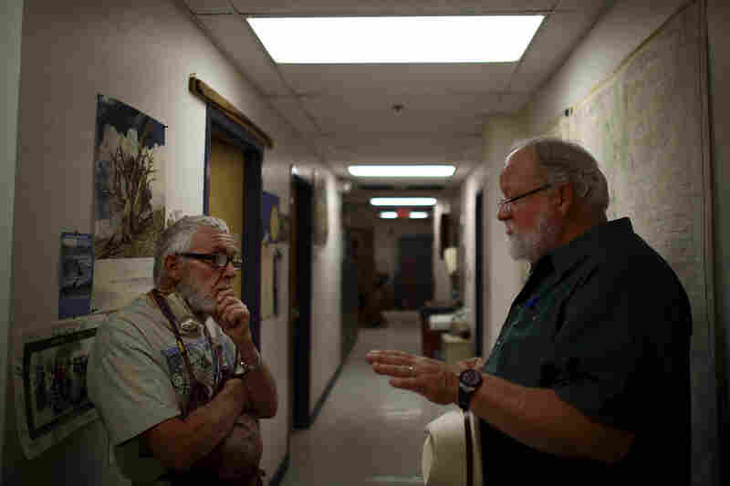 Adams (left) talks with Swetnam in their laboratory, nestled under the football stadium.