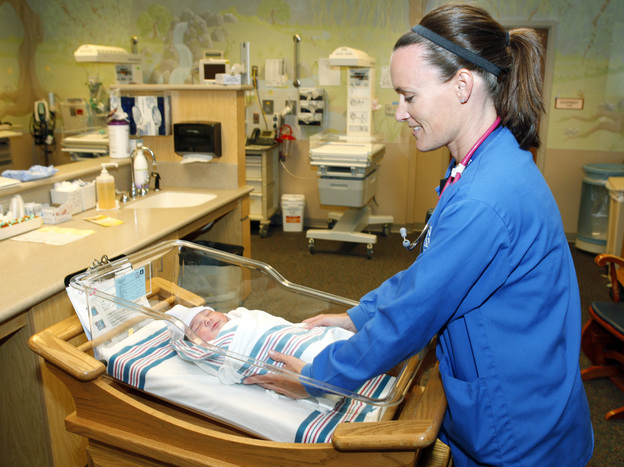 Nurse Angie Hagen tends to a newborn boy in the nursery at Denver Health medical facility in Denver in June 2011. The following month Colorado ended coverage for routine circumcisions under Medicaid. (AP)