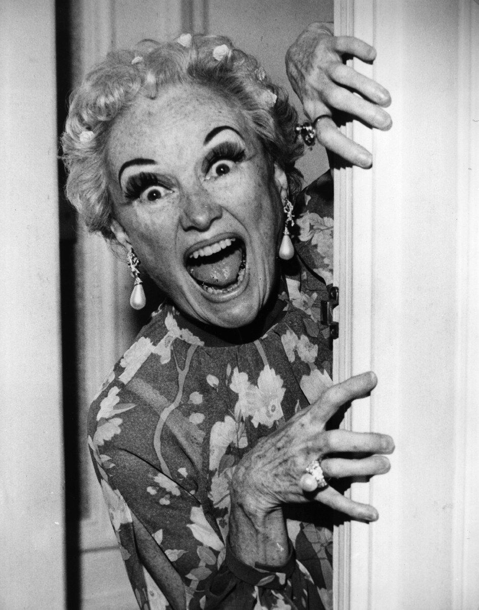 Phyllis Diller plays peekaboo with the cameraman before the start of her television show <em>Bonkers</em> in 1979.