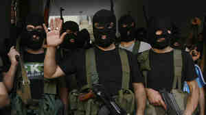 Lebanese masked gunmen from the al-Mokdad clan gather for a news conference in Beirut's southern suburbs on Aug. 15. The Mokdads, a large Lebanese Shiite Muslim clan, said they kidnapped at least 20 Syrians to try to secure the release of a family member abducted by Syrian rebels near Damascus this week.