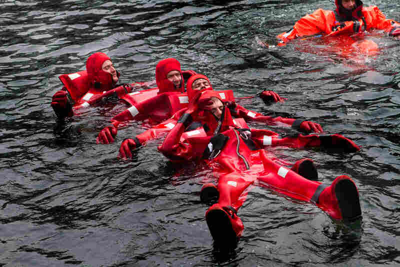 """In a formation called """"the worm,"""" crewmen link up to be able to paddle against strong waves and winds to a lifeboat."""