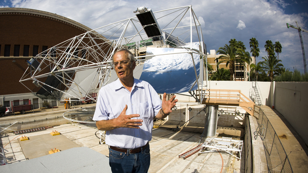 Roger Angel, an astronomer at the University of Arizona, stands in front of his new project: a solar tracker. Angel wants to use the device to harness Arizona's abundant sunlight and turn it into usable energy. (Jason Millstein for NPR)