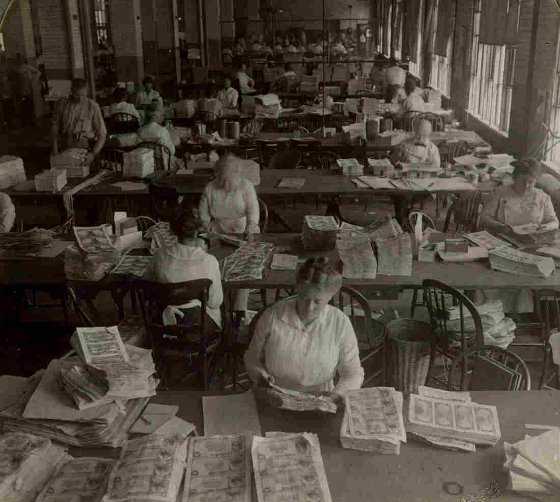 Workers inspecting sheets of money for printing flaws and smudges, circa 1917. Approved sheets received serial numbers and U.S. Treasury seals.