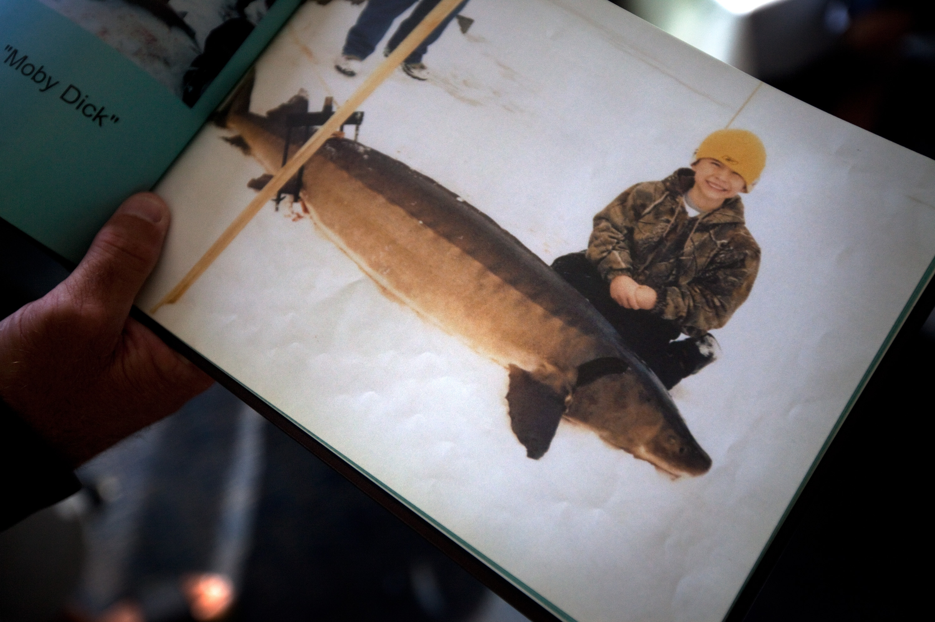 Shawn Wendt shows off a picture of his son Zach with a sturgeon that was speared and caught through the ice on Lake Winnebago. Sturgeon spearing is a popular winter sport in the area.