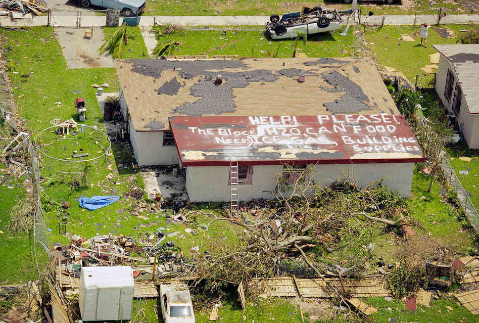 "A resident of Homestead, Fla., asks for help on Aug. 26, 1992, two days after the area was ravaged by Hurricane Andrew. The sign on the roof reads, ""Help please! The block needs H20, can food, ice, gas, building supplies."" Homestead was one of the hardest hit areas."