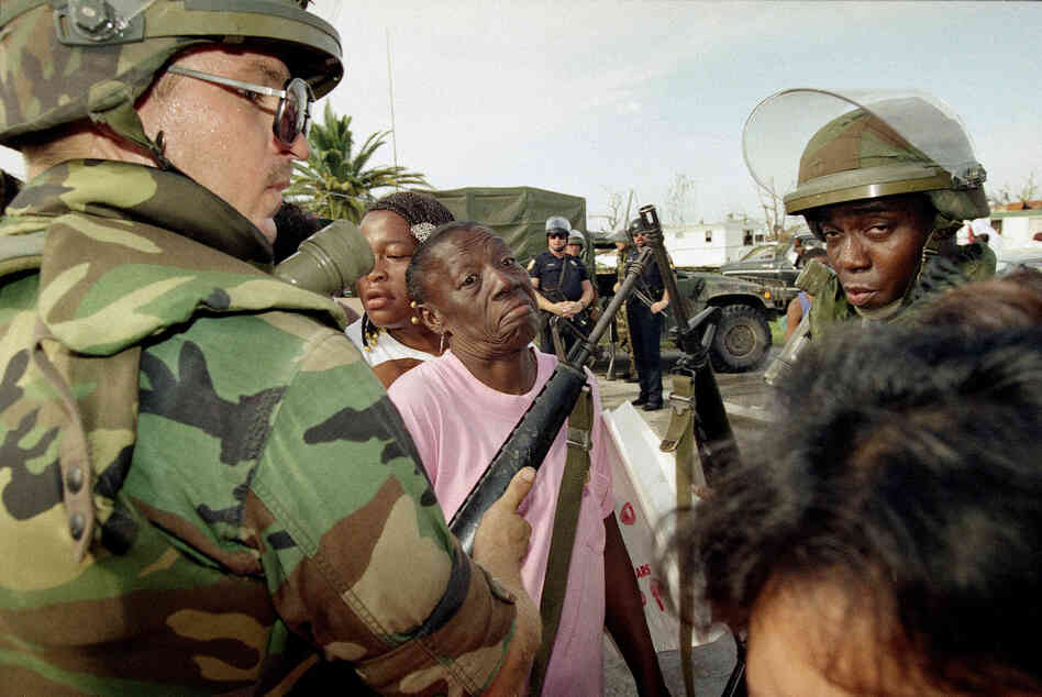 Florida National Guardsman Sgt. Jim Urbanik of Tampa holds out his gun to keep people in line as they wait for food at a distribution center in Florida City. Many residents of the south Dade County farming community lost their homes.