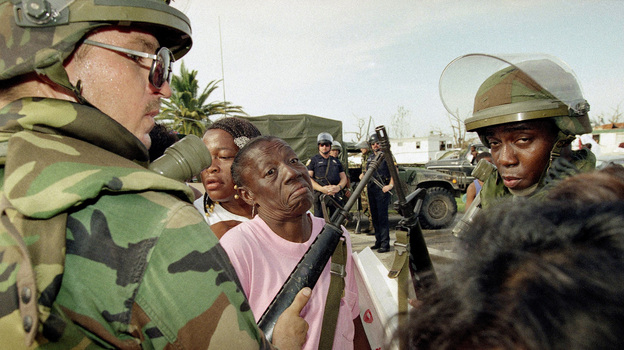 Florida National Guardsmen keep people in line at a food distribution center in Florida City, Fla., on Aug. 27, 1992. Many residents of the Dade County farming community lost their homes to Hurricane Andrew. (AP)