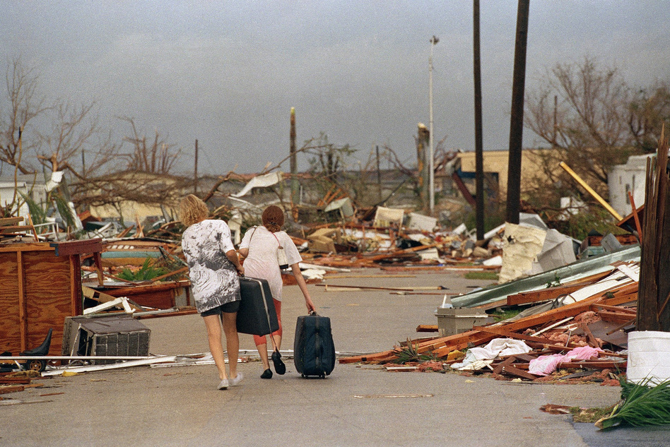 Joan Wallach (left) and her daughter, Brenda, carry possessions they salvaged from their trailer as they walk through the debris that was the Royal Palm Trailer Court in Homestead. (AP)